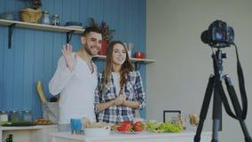 快乐的有吸引力的关于在家烹调的夫妇录音录影食物博克在dslr照相机在厨房里 免版税库存图片