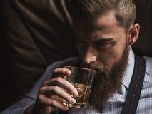 快乐的有胡子的商人喝昂贵的威士忌酒 库存照片