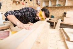 快乐的有胡子的木工是感人的板条 图库摄影