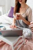 快乐的有茶的妇女运转的膝上型计算机 库存照片