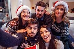 快乐的朋友做在新年` s前夕的滑稽的面孔 库存照片