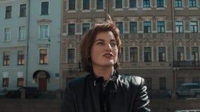 快乐的歌手女孩在黑皮夹克的老镇执行 影视素材