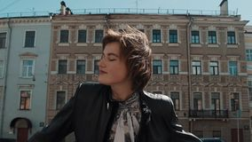 快乐的歌手女孩在黑皮夹克的老镇执行 股票视频