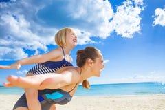 快乐的母亲和女儿有的海岸的乐趣时间 图库摄影