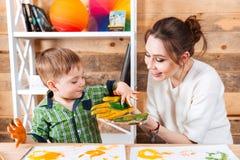 快乐的母亲和她小的儿子绘画在他们的手上 库存图片