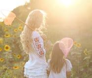快乐的母亲和她的女儿在夏天晚上 库存图片