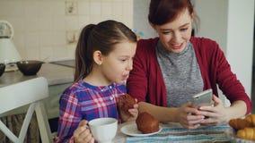 快乐的母亲和逗人喜爱的女儿浏览智能手机一起和微笑在早餐期间早晨在厨房里在 影视素材