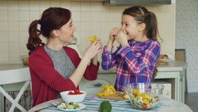 快乐的母亲和逗人喜爱的快乐的女儿有乐趣做鬼脸傻与菜,当在家时烹调在厨房 股票视频