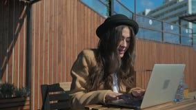 快乐的深色的女孩在笔记本键盘键入,坐户外 股票录像