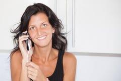 快乐的深色的少妇与手机,棕褐色的秀丽女孩在家讲话在房子里 免版税库存照片