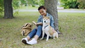 快乐的混合的族种女孩狗所有者是阅读书和抚摸她逗人喜爱的小狗坐草在公园在夏日 股票录像