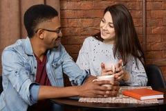 快乐的混合的族种女朋友射击和男朋友有日期在咖啡馆,坐在与红色课本,饮料热的饮料的桌上 库存图片