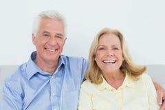 快乐的爱恋的资深夫妇坐沙发 图库摄影