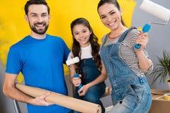 快乐的父亲、母亲和小女儿在投入的它房子里做小整修在销售中 免版税库存图片