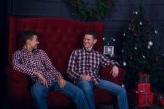 快乐的父亲和儿子在圣诞树前面坐 库存照片