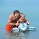快乐的父亲和儿子游泳在可膨胀的玩具的海 免版税库存照片