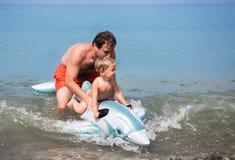 快乐的父亲和儿子游泳在可膨胀的玩具的海 免版税库存图片