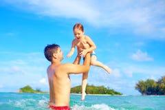 快乐的父亲和儿子获得乐趣在热带海滩的水中 免版税图库摄影
