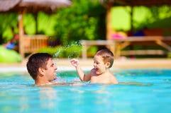 快乐的父亲和儿子获得乐趣在水池,暑假 免版税图库摄影