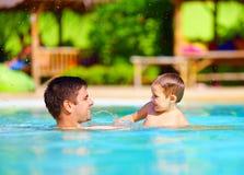 快乐的父亲和儿子获得乐趣在水池,暑假 免版税库存图片