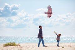 快乐的父亲和儿子,发射在沙滩的家庭风筝,大风天 图库摄影