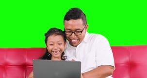 快乐的父亲和女儿使用在沙发的膝上型计算机 股票录像