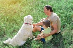 快乐的父亲和孩子获得与小狗的乐趣本质上 库存图片