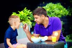 快乐的父亲哺养的儿子用鲜美水果沙拉 免版税库存图片