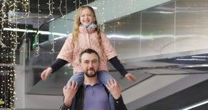 快乐的爸爸在她的肩膀在一个购物中心拿着一位美丽的女小学生 影视素材