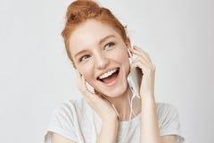 快乐的狡猾的在耳机微笑的女孩欣喜听的音乐 免版税库存图片