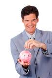 快乐的生意人节省额货币在贪心银行中 库存图片