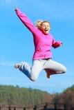 快乐的田径服跳跃的显示的妇女十几岁的女孩室外 免版税图库摄影