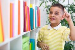 快乐的男孩学生有想法在图书馆 免版税图库摄影