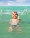快乐的男孩游泳在海运 免版税库存图片