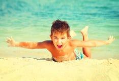 快乐的男孩获得乐趣在海滩 免版税库存照片