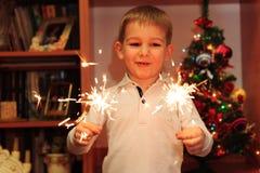 快乐的男孩观看的闪烁发光物 库存照片