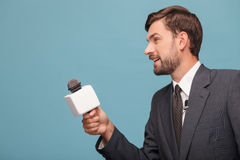 快乐的男性新闻广播员工作与人 免版税图库摄影