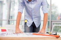 快乐的男性建筑师在办公室工作 免版税库存图片