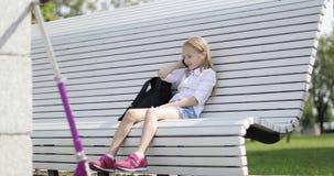 快乐的白肤金发的女孩坐一条长凳在公园和谈话在一个手机 股票视频