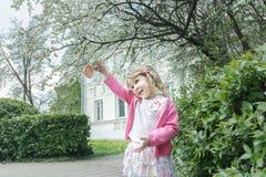 快乐的白肤金发的女孩室外画象开花的果树和门廊背景的 免版税库存照片