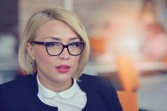快乐的白肤金发的妇女画象在办公室 免版税图库摄影