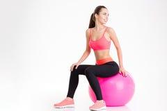 快乐的相当年轻健身妇女坐桃红色fitball 库存照片