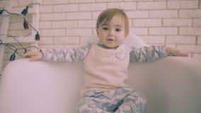快乐的矮小的深色的女婴坐与微笑慢动作的白色椅子 影视素材