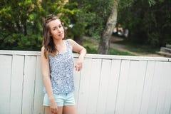 年轻快乐的站立女孩佩带的短裤室外 免版税库存图片