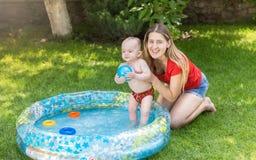 快乐的笑的母亲画象有使用在可膨胀的游泳池的男婴的 库存图片