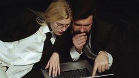 快乐的精力充沛的女商人和商人有计算机的使用互联网 企业夫妇概念 谈话和 股票录像