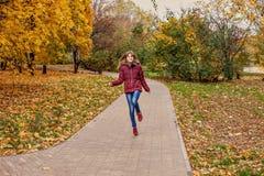 快乐的红发女孩通过秋天公园跑跳 图库摄影