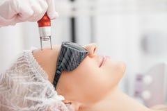 快乐的纯熟美容师对待女性 免版税库存图片