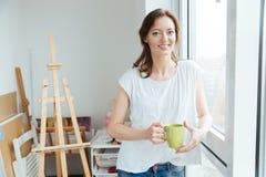 快乐的美丽的在窗口附近的妇女画家饮用的茶 免版税库存照片