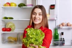 快乐的美丽的女性在手上拿着沙拉莴苣,支持健康营养,站立近的冰箱 选择聚焦 敬慕 库存照片